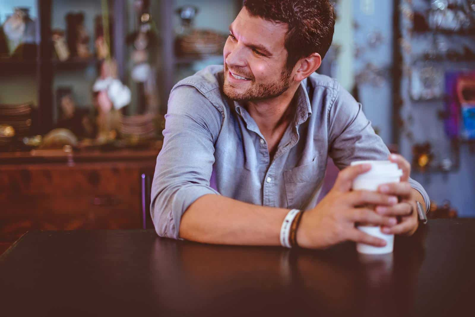 Man smiling and having coffee